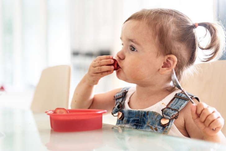 Little 2 years old girl eating jello