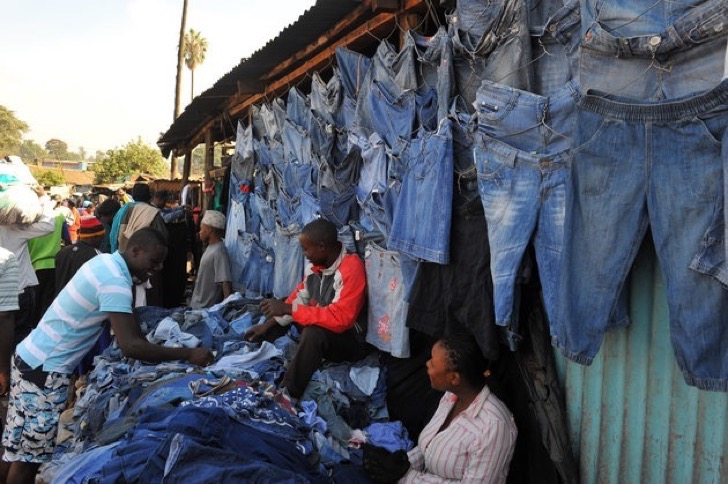 """A man samples second-hand clothes (locally known as mitumba) at the Gikomba open-air market on June 25, 2012, in Nairobi. Local dealers welcomed Kenya's Finance minister Njeru Githai's move to lower import duty on """" Mitumba"""" in this year's budget read two weeks ago. However, trade experts say the reduction on import duty, will put over 270,000 jobs in the cotton industry at risk and lives of farmers as well. AFP PHOTO/SIMON MAINA (Photo credit should read SIMON MAINA/AFP/GettyImages)"""