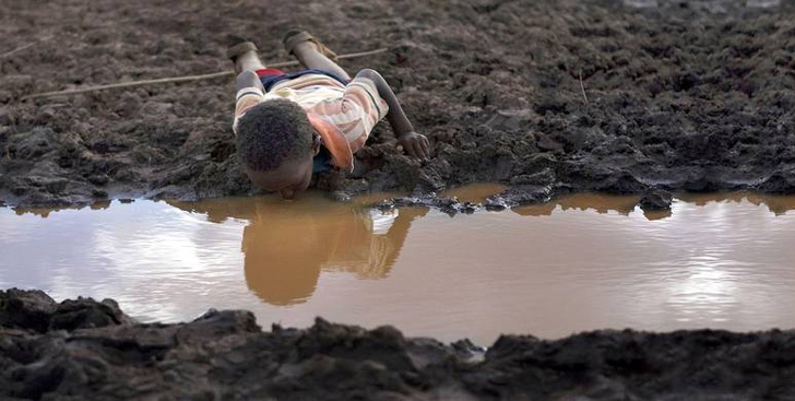 Small African boy laying in the mud, sucking water from a muddy puddle