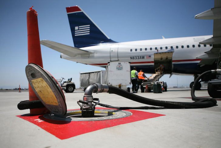 OAKLAND, CA - JULY 18: A fuel line connected to an underground tank is seen near a US Airways plane July 18, 2008 at the Oakland International Airport in Oakland, California. US Airways pilots and its dispatchers, who calculate fuel loads, are involved in a dispute that has pilots claiming that they are being pressured to fly with less fuel to cut costs as fuel prices continue to rise and cripple earnings. (Photo by Justin Sullivan/Getty Images)